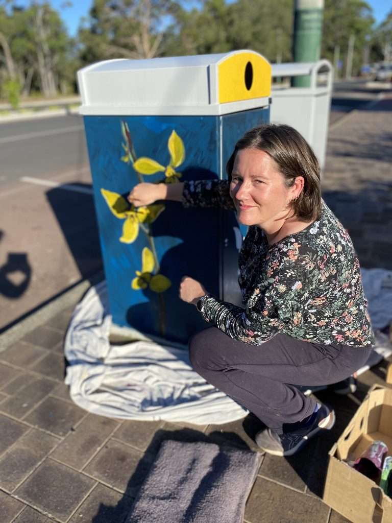 Alicia Rogerson painting her Tall Donkey Orchid design as part of the Blooming Wild Bins project in Northcliffe
