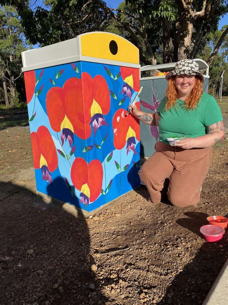 Tara Brooks painting her Northcliffe Kennedia design as part of the Blooming Wild Bins project in Northcliffe